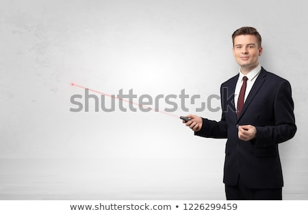 Foto stock: Businessman with laser pointer and copyspace white wall