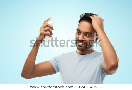 smiling indian man applying hair spray Stock photo © dolgachov