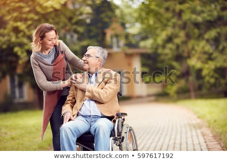 Hands of an old woman and a young man. Caring for the elderly. close up Stock photo © galitskaya