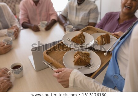 Mid section of female doctor holding tray of cake to bring it to senior people at home Stock photo © wavebreak_media