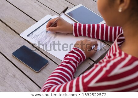 Overhead mid section view of a African American woman filling a form on her terrace at home Stock photo © wavebreak_media