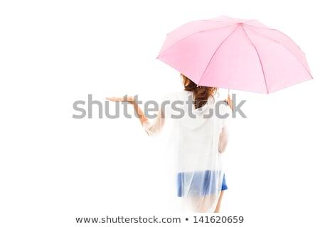 Beautiful young woman in raincoat with umbrella checking for rain Stock photo © elenaphoto