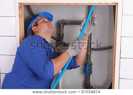 Plumber feeding blue flexible pipe behind a tiled wall Stock photo © photography33