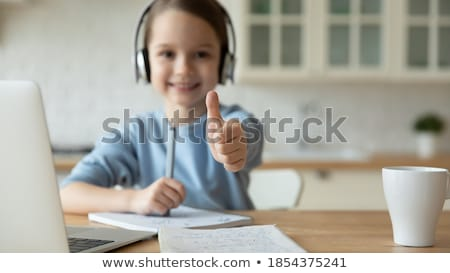 portrait of a cute schoolgirl with the thumb up with the camera focus on the thumb stock photo © wavebreak_media