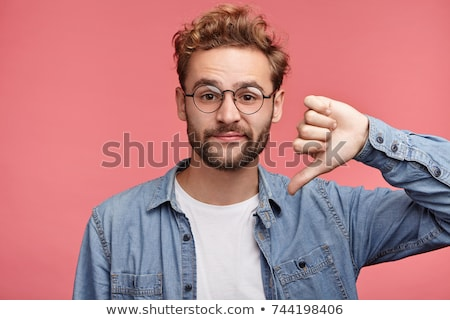 casual young man shows thumb down stock photo © feedough