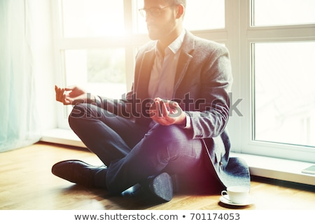Businessman meditating in the office Stock photo © Elnur
