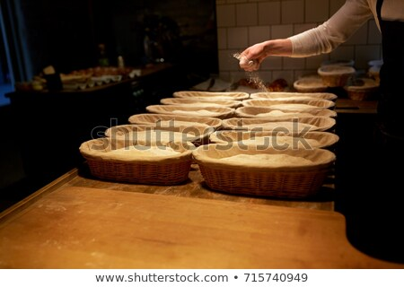 baker with dough rising in baskets at bakery Stock photo © dolgachov