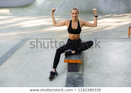 Sports woman sitting in park outdoors showing biceps. Stock photo © deandrobot