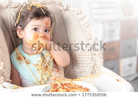 little baby girl eating in highchair at home Stock photo © dolgachov