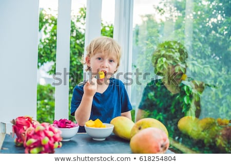 Weinig cute jongen eten mango terras Stockfoto © galitskaya