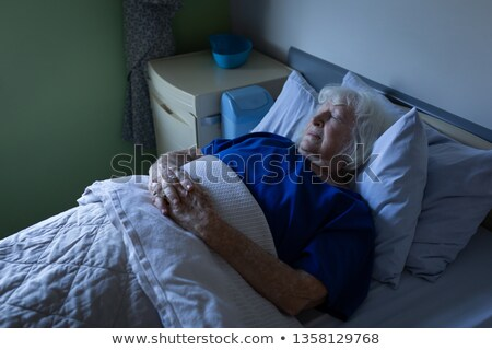 Side view of a senior Caucasian female patient sleeping with hands joined in a hospital bed at hospi Stock photo © wavebreak_media