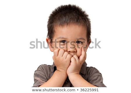 Preschool aged boy with his hand/fists over his mouth; looking e Stock photo © dacasdo