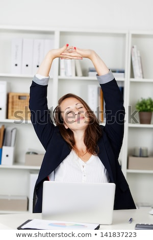 Woman sat at her desk stretching Stock photo © photography33