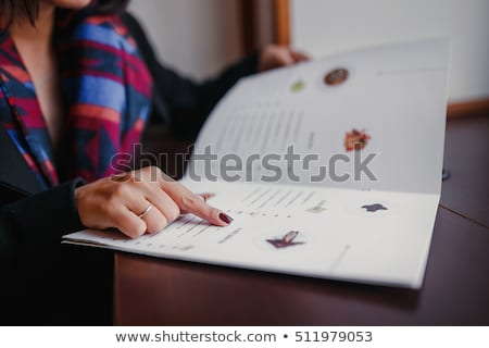 Stock photo: Woman reading a menu in a restaurant