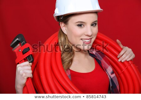 tradeswoman holding corrugated tubing and a pipe wrench stock photo © photography33