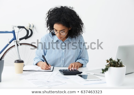 Businesswoman using a calculator at her desk Stock photo © photography33