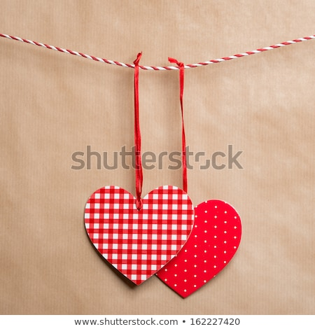 Two red textured hearts hanging on a ribbon. Old brown paper bac Stock photo © HASLOO
