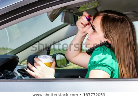 young woman applying makeup while in the car stock photo © nobilior