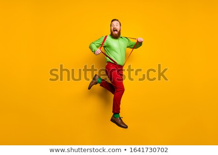 young fashion man pulling his pants up stock photo © feedough
