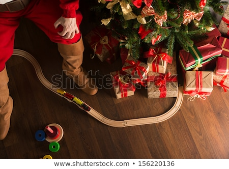Stock photo: Unrecognizable Santa Claus playing with wooden railroad near Chr