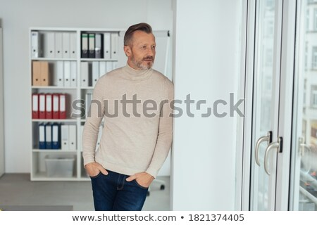 Thoughtful businessman standing against glass wall at office Stock photo © wavebreak_media