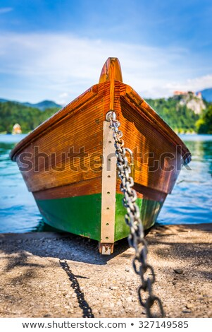 detail of anchored wooden tourist boat on shore of bled lake sl stock photo © kayco