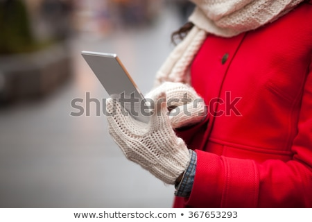 Woman in red coat and wool cap and gloves with smartphone in han Stock photo © adamr