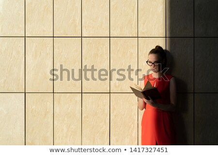 attractive man standing and reading book in the evening stock photo © deandrobot