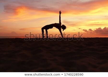 Woman in half moon yoga pose meditating at sunset. Zen Stock photo © photocreo
