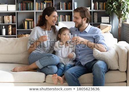 Stock photo: Happy young couple holding drink glasses