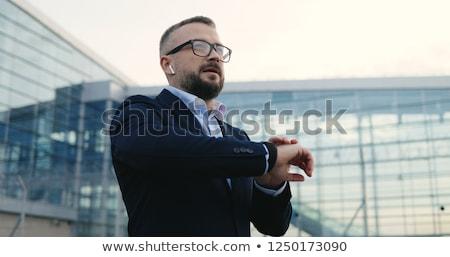 caucasian man wearing glasses using his watch stock photo © deandrobot