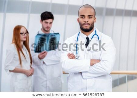 Retrato doctor de sexo masculino uniforme pie armas doblado Foto stock © deandrobot