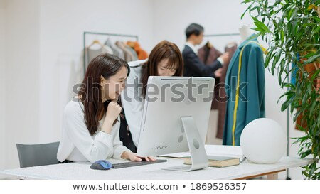 Three cute young women clothes designers working Stock photo © deandrobot