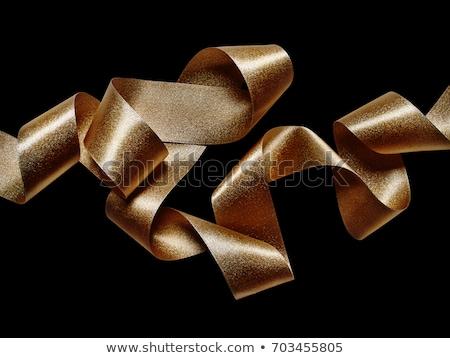 gold serpentine metallic ribbons on black background stock photo © marysan