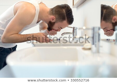 Male Hand Rinsing Toothbrush With Water In Bathroom Stock photo © diego_cervo