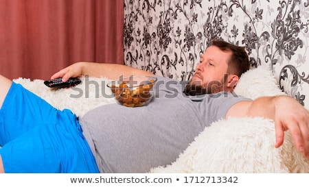 close up of man with tv remote drinking beer Stock photo © dolgachov