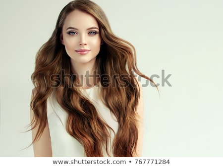 Stock photo: Studio portrait of pretty brunette girl with long wavy hair taking self portrait on her smart phone.
