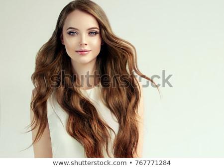 Studio portrait of pretty brunette girl with long wavy hair taking self portrait on her smart phone. stock photo © studiolucky