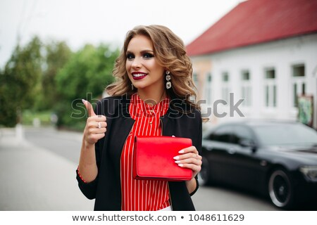 Smiling girl demonstrating handbag with thumb up. stock photo © studiolucky
