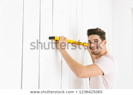 Image of young guy 20s holding big ruler at white wall, while me Stock photo © deandrobot