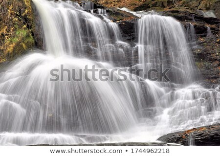 Powerful waterfall flowing down cliff ledge Stock photo © lovleah