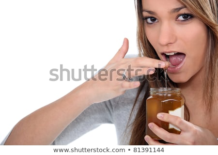Woman dipping finger in honey jar Stock photo © photography33