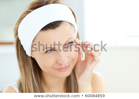 Young woman putting cream on her face wearing a headband in the bathroom at home stock photo © wavebreak_media