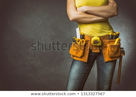 confident woman with helmet and belt of tools stock photo © stockyimages