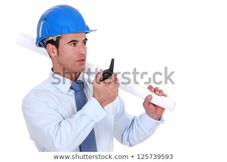 Engineer holding a rolled-up plan and speaking into a walkie-talkie Stock photo © photography33