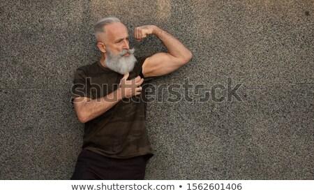 casual man outdoor flexes his biceps stock photo © feedough