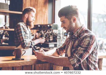 young man with a smartphone in a rustic place Stock photo © nito