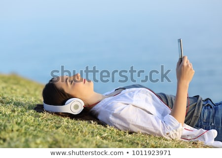 Stock photo: Woman with closed eyes and smile using headphones