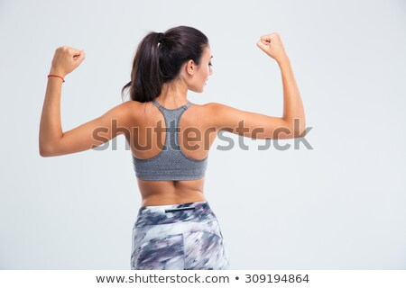 back view portrait of a fitness woman showing her biceps stock photo © deandrobot