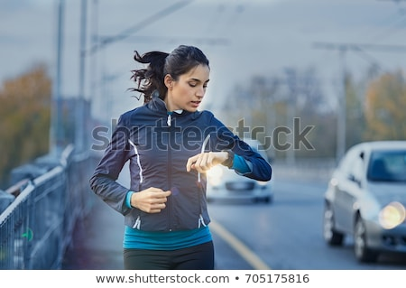 Young fitness woman looking at her smart watch while taking a br Stock photo © boggy